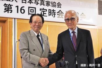 田沼武能・前会長(左)と握手する熊切圭介・新会長(右)