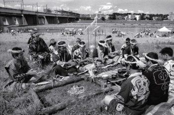 カムイノミ(神への祈り)は、キャンプを楽しむ人びとで賑わう、多摩川河川敷で行なわれた。(1999.8.8)撮影:宇井眞紀子