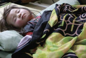 アイヌ文様の刺しゅうが入った着物をかけて、工芸品展示会会場の片隅で眠る女の子。(2008.4.26)撮影:宇井眞紀子